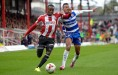 Moses Odubajo of Brentford is challenged by Jordan Obita of Reading. Skybet football league championship match, Brentford v Reading at Griffin Park in London on Saturday 4th Oct 2014. pic by John Patrick Fletcher, Andrew Orchard sports photography.